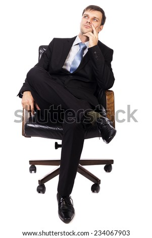 Thoughtful businessman sitting in  armchair and looking up isolated over white background
