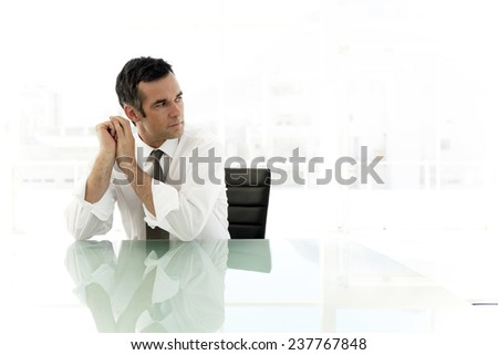 Thoughtful Businessman sitting in meeting room - stock photo