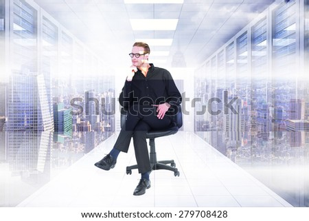 Thoughtful businessman sitting on a swivel chair against server room with towers - stock photo