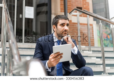 Thoughtful businessman sitting on steps with tablet pc