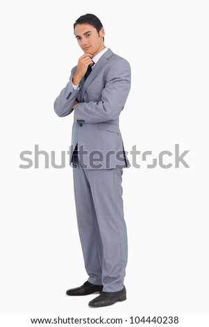 Thoughtful businessman smiling with folded arms against white background