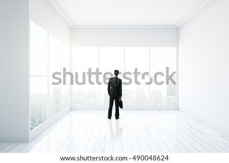 Thoughtful businessman standing in minimalistic interior design with white walls, floor, ceiling and panoramic windows with city view. 3D Rendering