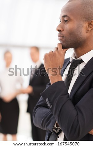 Thoughtful businessman.  Thoughtful young African man in formalwear holding hand on chin and looking away while his colleagues  standing on background - stock photo