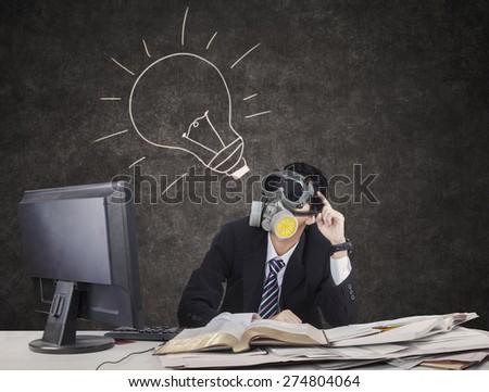 Thoughtful businessman wearing gas mask with lightbulb on blackboard - stock photo