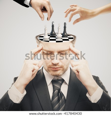 Thoughtful businessman with chess board instead of brain and two businesspeople hands having a chess tournament with currency sign pawns on light background - stock photo