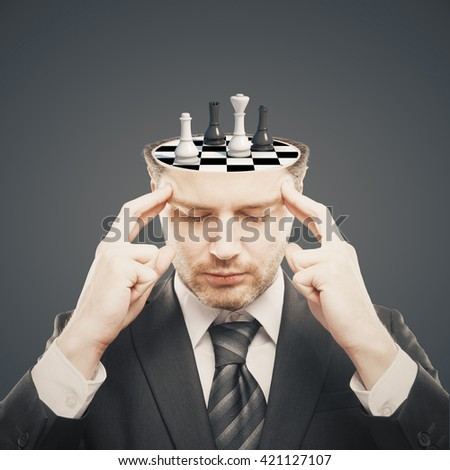 Thoughtful businessman with chess board instead of brain on grey background. Brainstorming concept