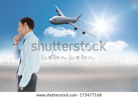 Thoughtful businessman with hand on chin against cityscape on the horizon