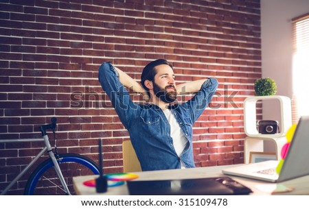 Thoughtful businessman with hands behind back relaxing in creative office - stock photo