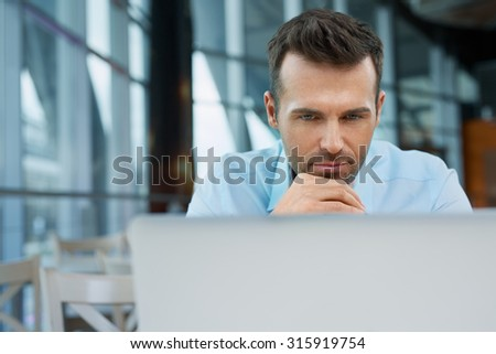 Thoughtful businessman working on laptop at modern office - stock photo