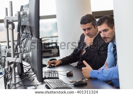 Thoughtful businessmen trading stocks in corporate office.. Concerned stock traders looking at graphs, indexes and numbers on multiple computer screens. Business crisis and loss concept. - stock photo