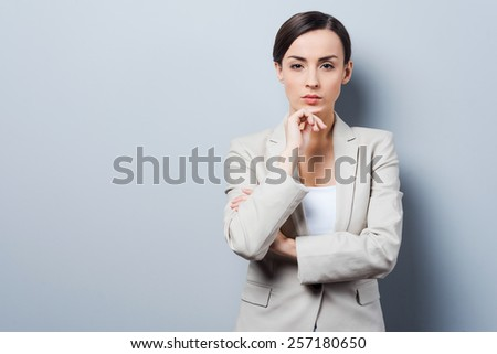 Thoughtful businesswoman. Confident young businesswoman keeping arms crossed and looking at camera while standing against grey background - stock photo