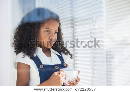 Thoughtful businesswoman holding coffee cup seen through window