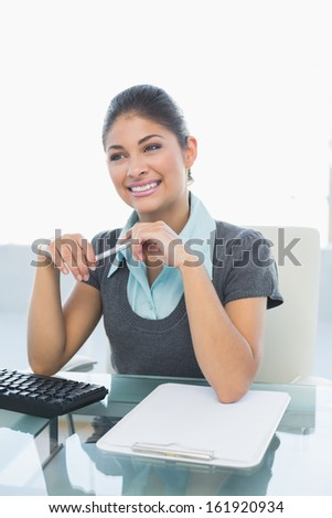 Thoughtful businesswoman looking away while using computer on desk in a bright office