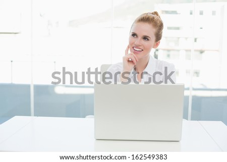 Thoughtful businesswoman looking up while using laptop on desk in a bright office