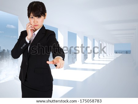 Thoughtful businesswoman pointing against bright white hall with columns