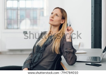 Thoughtful businesswoman pondering a problem as she swivels in her chair to look pensively up at the ceiling