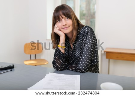 Thoughtful businesswoman sitting at her desk with her chin resting on her hand smiling at the camera - stock photo