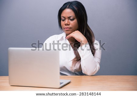 Thoughtful businesswoman sitting at the table and using laptop over gray background - stock photo