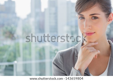 Thoughtful businesswoman smiling at camera beside large window - stock photo
