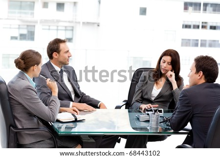 Thoughtful businesswoman talking to her team during a meeting at work - stock photo