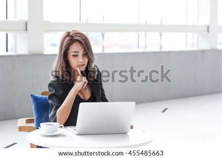 thoughtful businesswoman using laptop while sitting on the table with a cup of coffee in office building