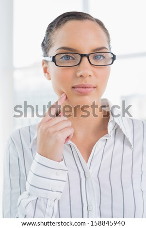 Thoughtful businesswoman wearing reading glasses looking at camera