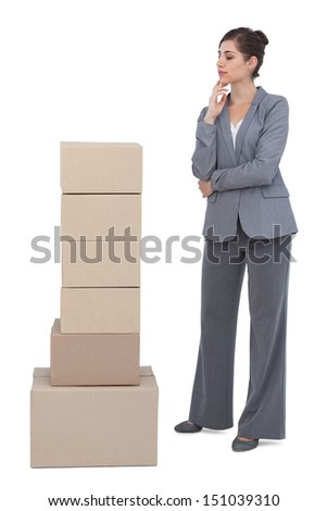 Thoughtful businesswoman with cardboard boxes on white background  - stock photo