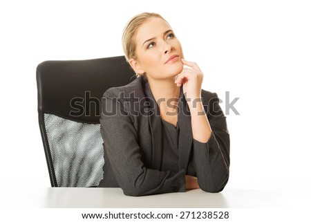 Thoughtful businesswoman with hands onc hin - stock photo