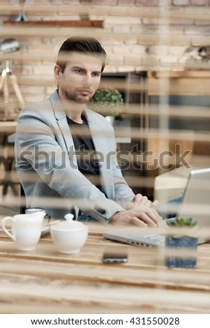 Thoughtful busy businessman working at desk, behind shutter, using laptop computer. - stock photo