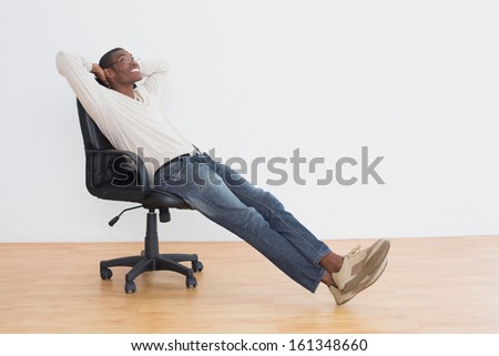 Thoughtful casual Afro young man sitting on office chair in an empty room