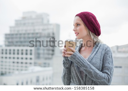 Thoughtful casual blonde holding coffee outdoors on urban background - stock photo