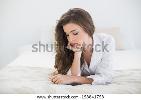 Thoughtful casual brown haired woman in white pajamas lying on her bed in a bright bedroom - stock photo