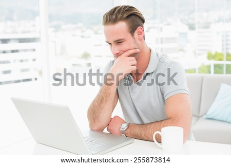 Thoughtful casual businessman working with laptop in his office