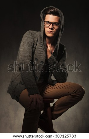 Thoughtful casual man sitting while holding one hand on his knee.