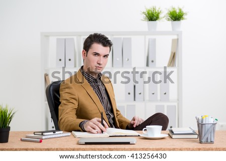 Thoughtful caucasian businessman in brown jacket sitting at office desk with various items - stock photo