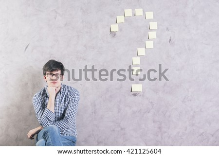 Thoughtful caucasian man sitting next to sticker question mark glued onto concrete wall - stock photo