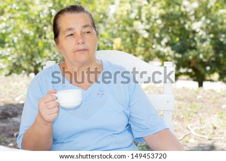 Thoughtful Caucasian mature woman wearing a blue T-shirt and holding a cup while sitting in the garden in a warm day of summer - stock photo