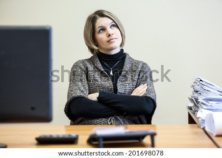 Thoughtful Caucasian woman secretary sitting at the table - stock photo