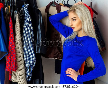 thoughtful charming blonde chooses clothes in shop. Beautiful young girl with a lot of clothes. Shopping concept. - stock photo