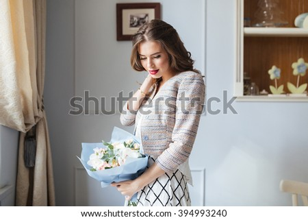 Thoughtful charming young woman standing near the window and holding bouquet of flowers - stock photo