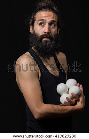 Thoughtful circus juggler with his balls miming during a performance - stock photo