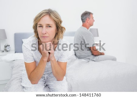 Thoughtful couple sitting on different sides of bed having a dispute with woman looking at camera in bedroom at home - stock photo