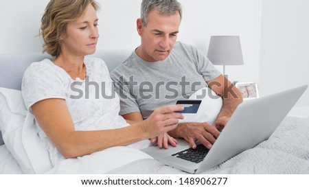 Thoughtful couple using their laptop to buy online at home in bedroom