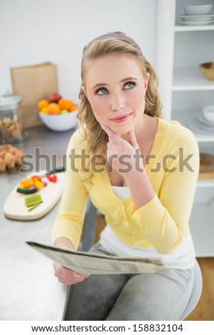 Thoughtful cute blonde holding newspaper in bright kitchen - stock photo