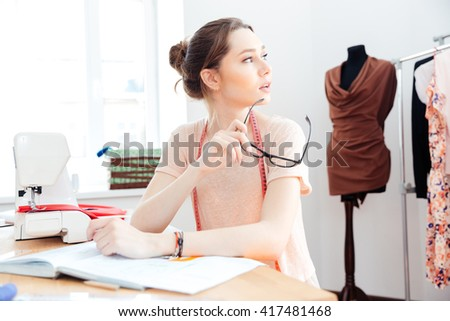 Thoughtful cute young woman seamstress sitting and thinking in workshop - stock photo