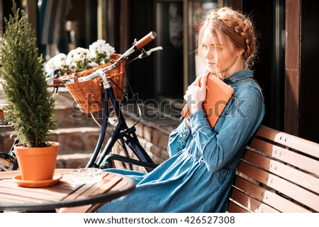Thoughtful cute young woman with bicycle readng book and dreaming on the beanch outdoors - stock photo