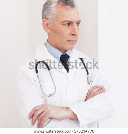 Thoughtful doctor. Senior grey hair doctor in uniform looking away and keeping hands clasped