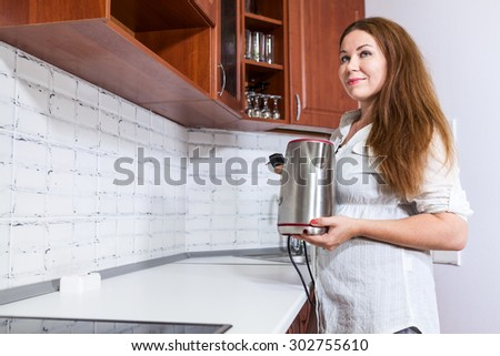 Thoughtful dreaming housewife with steel electric tea kettle in hands, domestic kitchen, copy space - stock photo