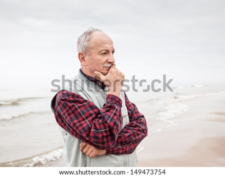 Thoughtful elderly man standing on the beach on a foggy day - stock photo
