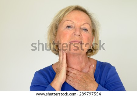 Thoughtful elderly woman with her hands to her neck looking at the camera with a serious pensive expression, head and shoulders over grey - stock photo